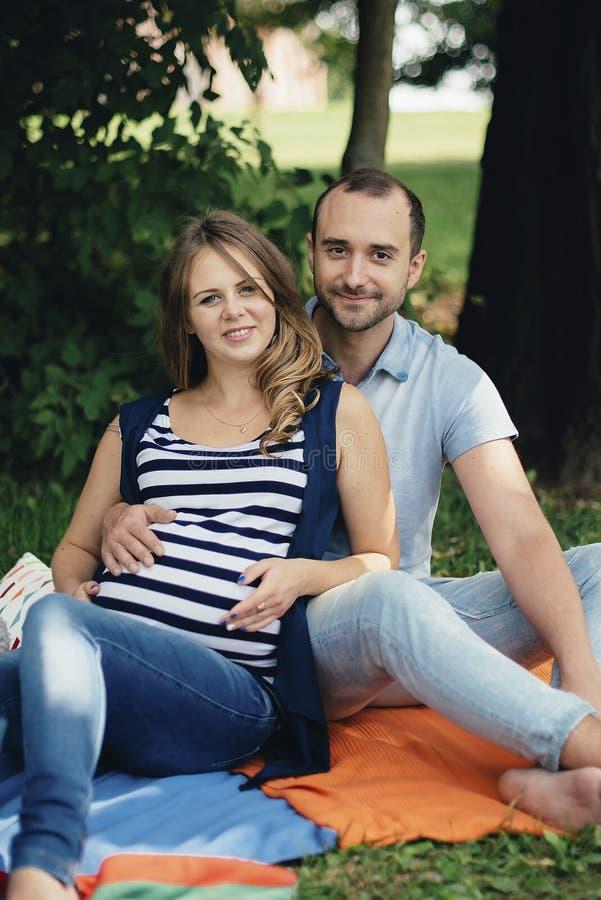 Hombre y mujer embarazada, en un par amoroso en el parque fotografía de archivo libre de regalías