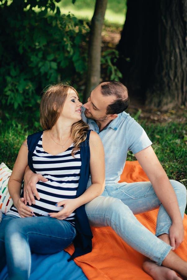 Hombre y mujer embarazada, en un par amoroso en el parque imagen de archivo libre de regalías