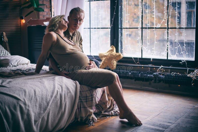 Hombre y mujer embarazada que se sientan en la cama en sitio del estilo del desván fotografía de archivo
