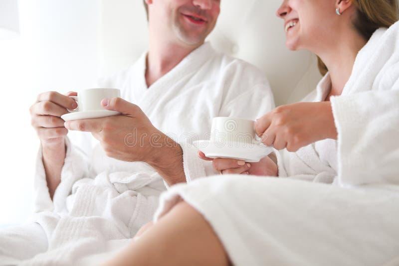 Hombre y mujer en albornoz en la cama imagen de archivo