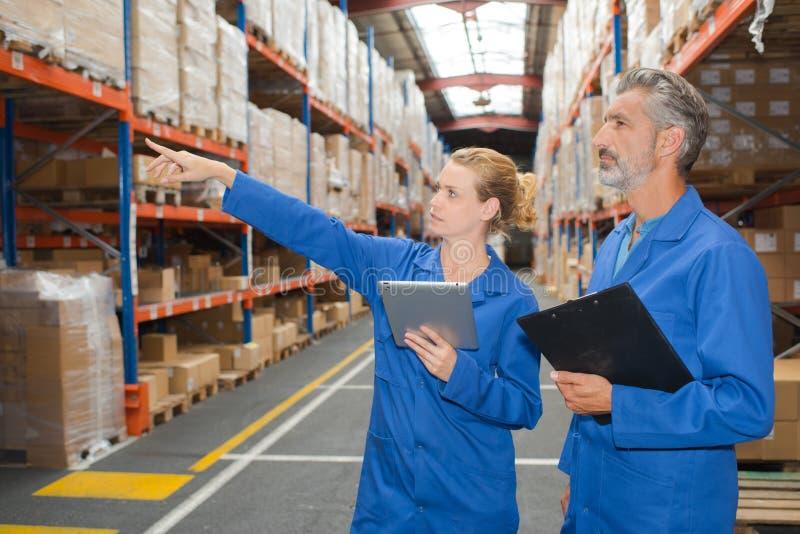 Hombre y mujer en almacén que señalan al estante imagenes de archivo