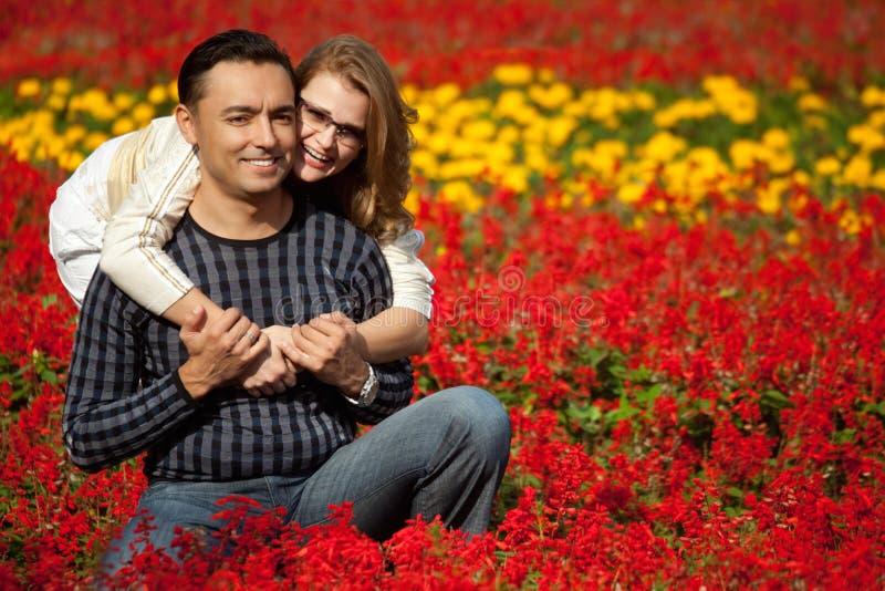 Hombre y mujer en corchetes que ríen en las flores fotografía de archivo