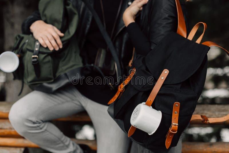 Hombre y mujer en el bosque Hombre y mujer con las mochilas y las tazas Caída de las tazas en la mochila Viaje Bosque imagen de archivo