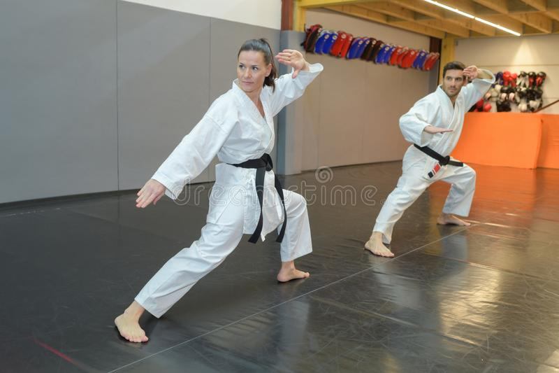Hombre y mujer en el karate blanco del entrenamiento de la correa negra del kimono imagen de archivo