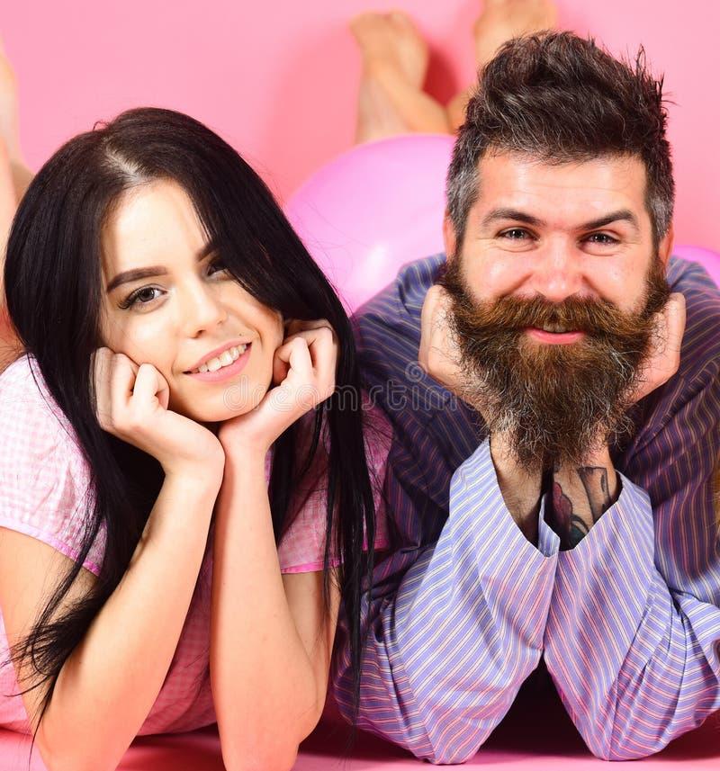 Hombre y mujer en la endecha sonriente de las caras, fondo rosado Pares en el amor feliz junto Hombre y mujer barbudos de la more fotos de archivo libres de regalías