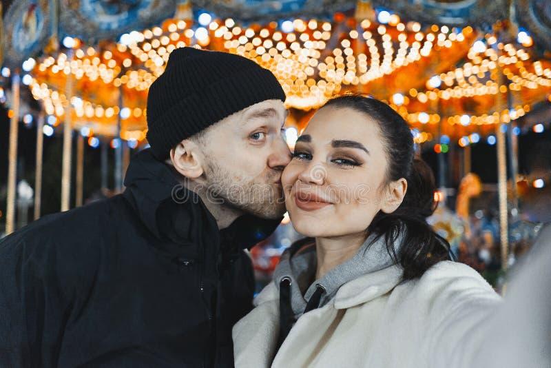 Hombre y mujer en la feria de la Navidad que besan y que hacen Selfie Relaciones felices foto de archivo