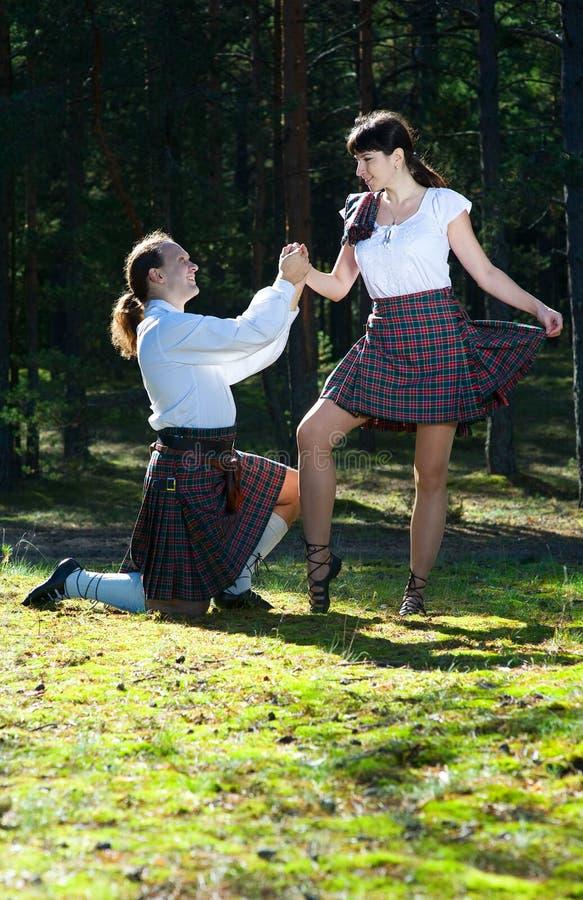 Hombre y mujer en traje escocés imagenes de archivo