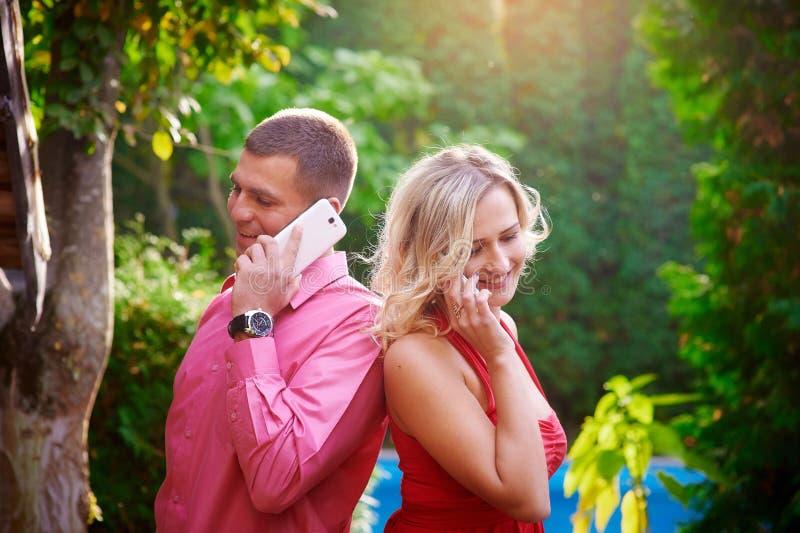Hombre y mujer en vestido rojo que hablan en el teléfono con uno a fotos de archivo