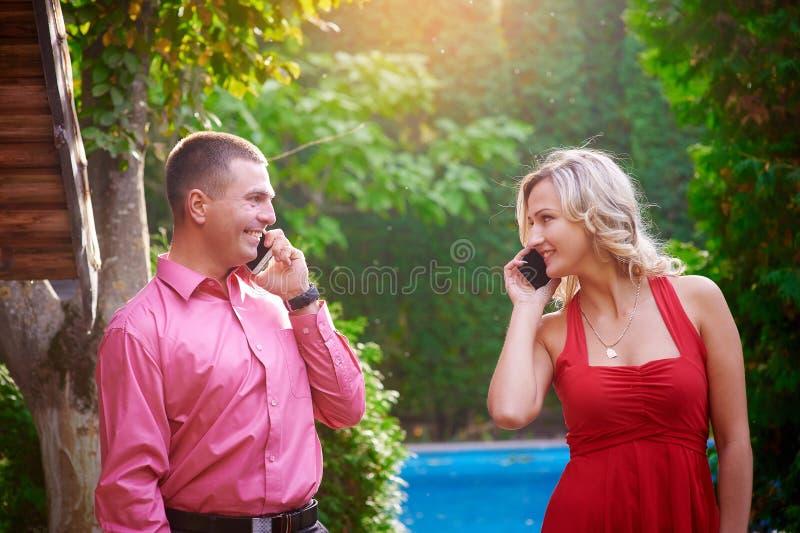 Hombre y mujer en vestido rojo que hablan en el teléfono con uno a imagen de archivo