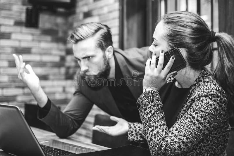 Hombre y mujer enojados subrayados de negocios con el ordenador portátil imagen de archivo