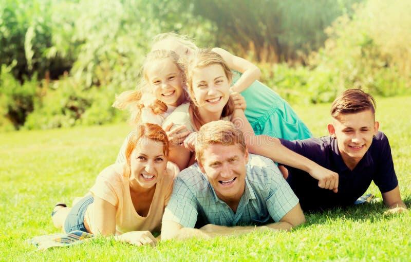 Hombre y mujer felices con cuatro niños que mienten en parque imagenes de archivo