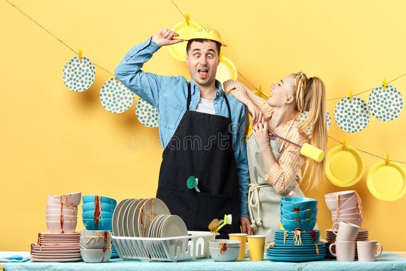 Hombre y mujer impresionantes en los delantales que se divierten mientras que lava los platos imágenes de archivo libres de regalías