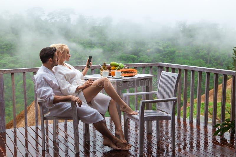 Hombre y mujer jovenes - desayuno de los pares en el balcón lluvioso foto de archivo
