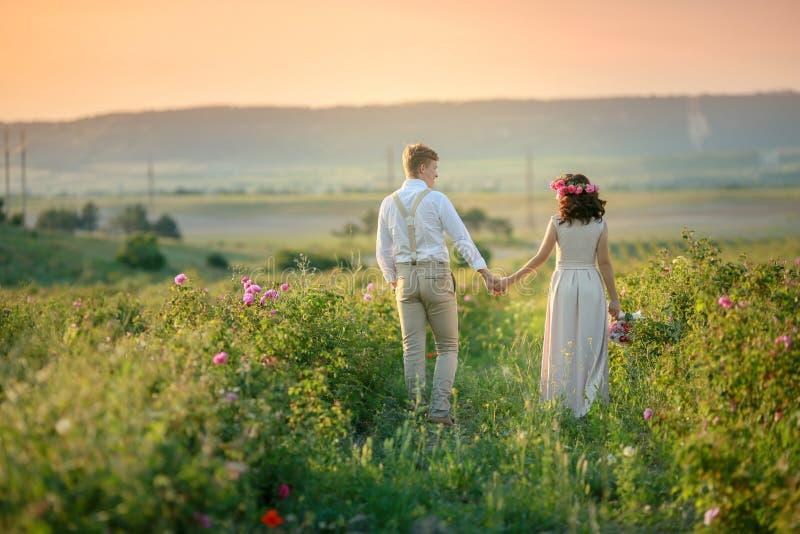 Hombre y mujer jovenes felices, familia romántica adulta de los pares Resuelva la puesta del sol en un campo de trigo Sonrisa fel imágenes de archivo libres de regalías
