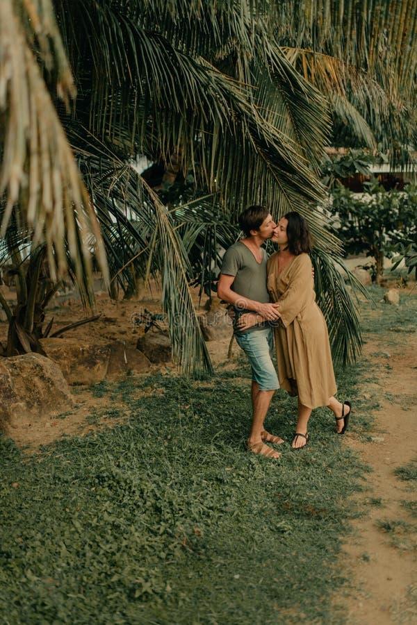 Hombre y mujer que abrazan debajo de las palmeras fotografía de archivo libre de regalías
