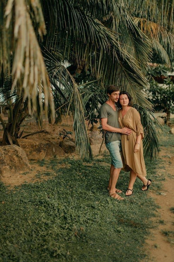 Hombre y mujer que abrazan debajo de las palmeras imagen de archivo