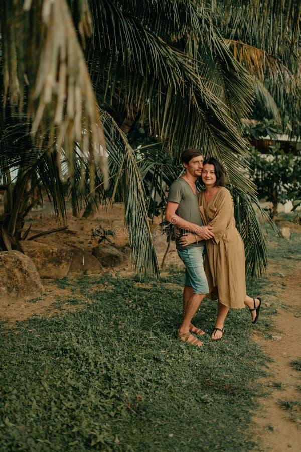 Hombre y mujer que abrazan debajo de las palmeras fotografía de archivo