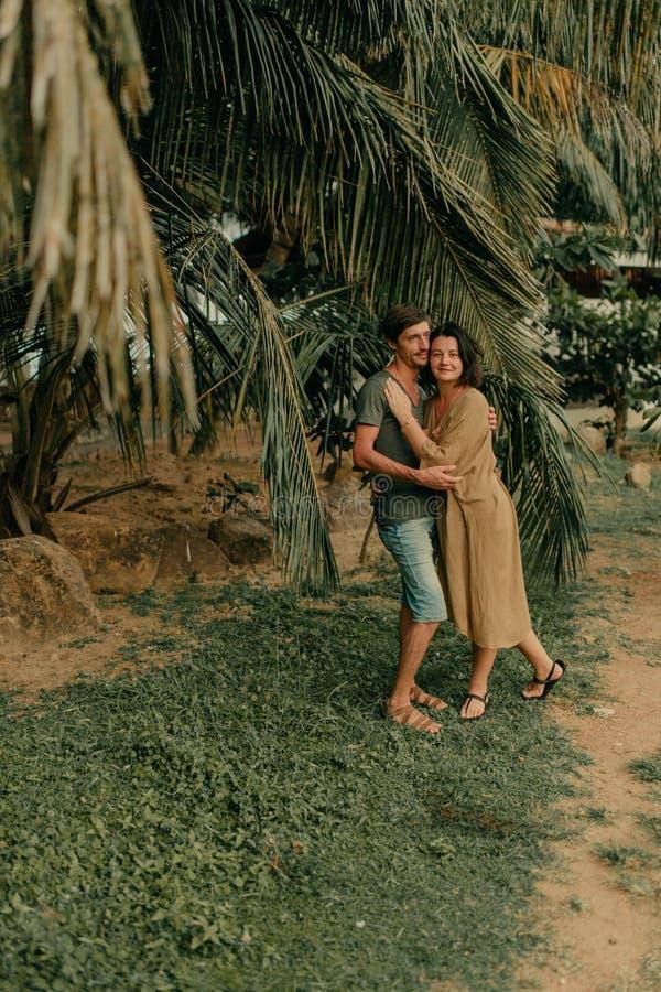Hombre y mujer que abrazan debajo de las palmeras foto de archivo