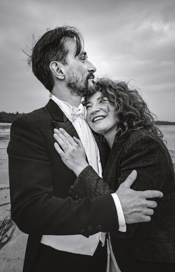Hombre y mujer que abrazan, en el fondo de la orilla de mar, día, al aire libre imágenes de archivo libres de regalías