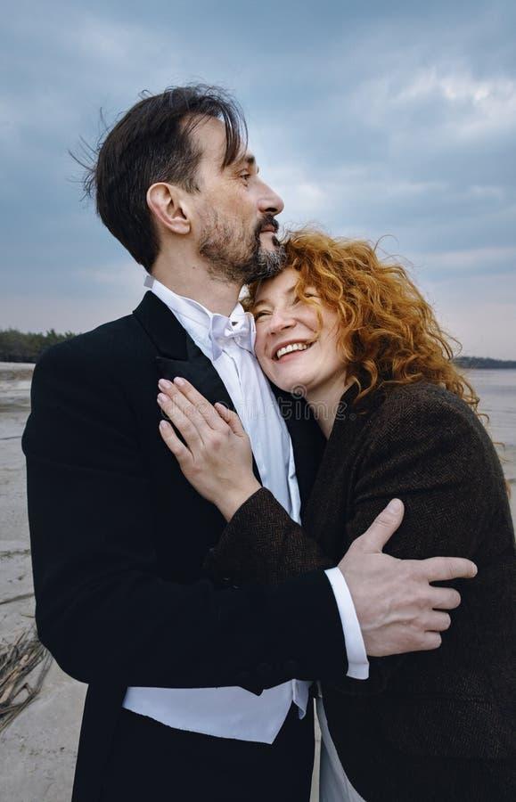 Hombre y mujer que abrazan, en el fondo de la orilla de mar, día, al aire libre fotos de archivo libres de regalías