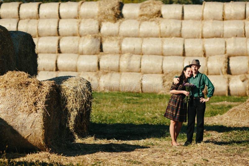 Hombre y mujer que abrazan en un campo fotos de archivo
