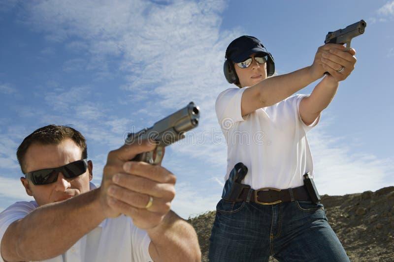 Hombre y mujer que apuntan los armas de la mano a la gama de leña imagen de archivo