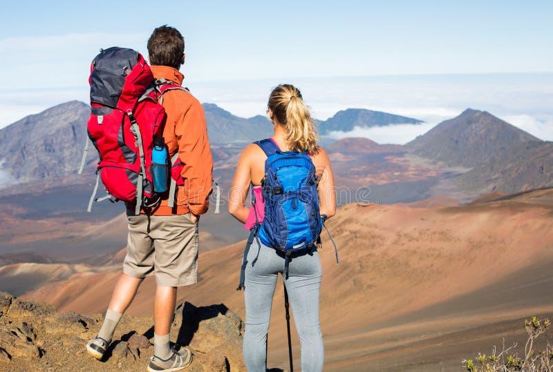 Hombre y mujer que caminan en rastro de montaña hermoso imagen de archivo