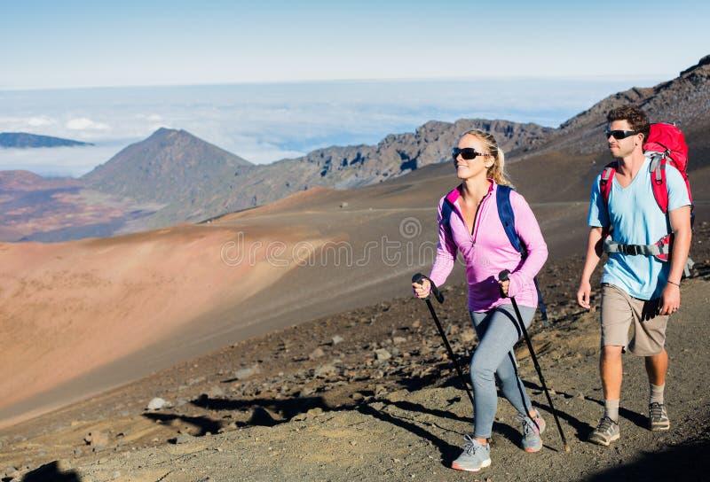Hombre y mujer que caminan en rastro de montaña hermoso imagenes de archivo