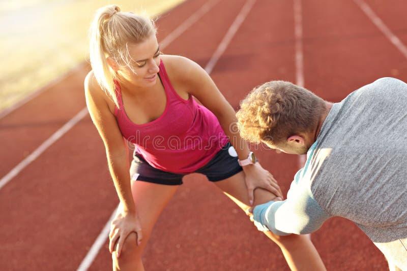 Hombre y mujer que compiten con en pista al aire libre imagen de archivo
