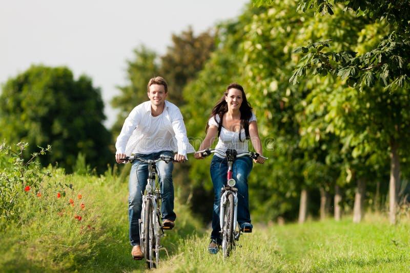 Hombre y mujer que completan un ciclo en verano imagen de archivo libre de regalías