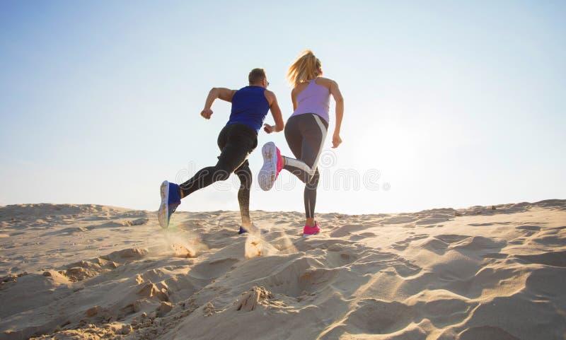 Hombre y mujer que corren en arena foto de archivo