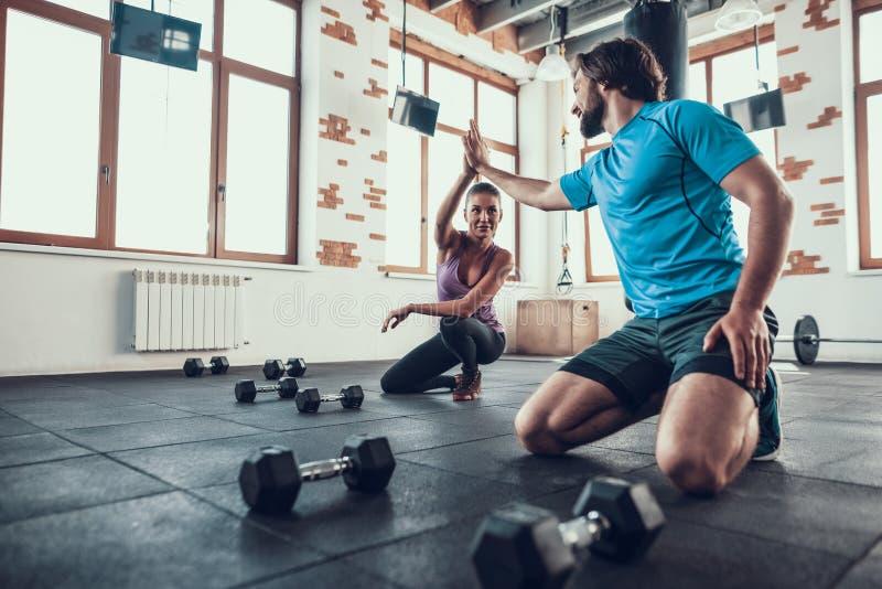 Hombre y mujer que dan altos cinco en club de fitness fotografía de archivo