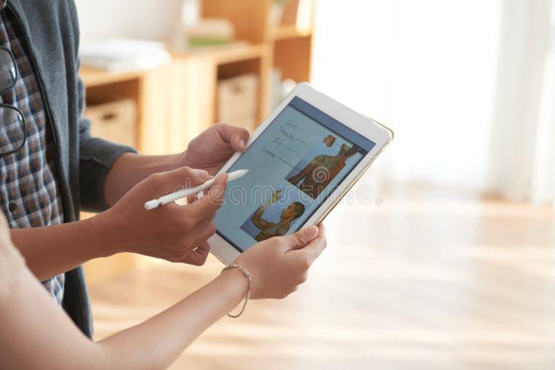 Hombre y mujer que discuten la imagen en la tableta foto de archivo