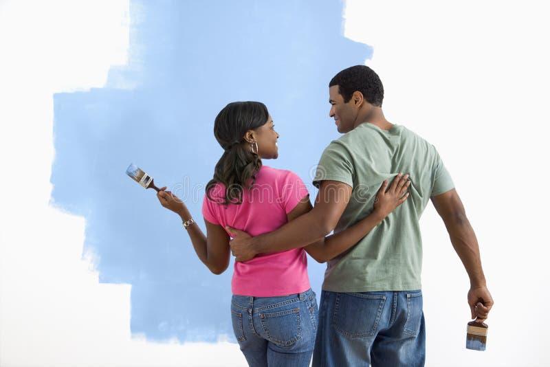 Hombre y mujer que discuten trabajo de la pintura. imagen de archivo
