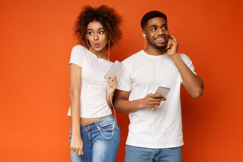 Hombre y mujer que disfrutan de música preferida en auriculares fotos de archivo