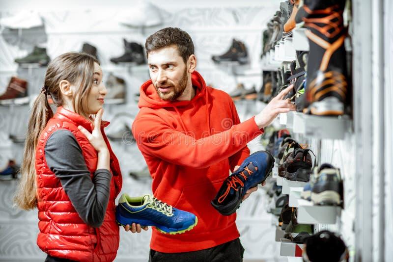 Hombre y mujer que eligen los zapatos en la tienda fotografía de archivo