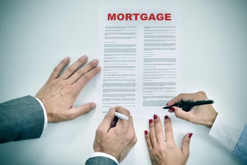 Hombre y mujer que firman un contrato de préstamo de hipoteca foto de archivo