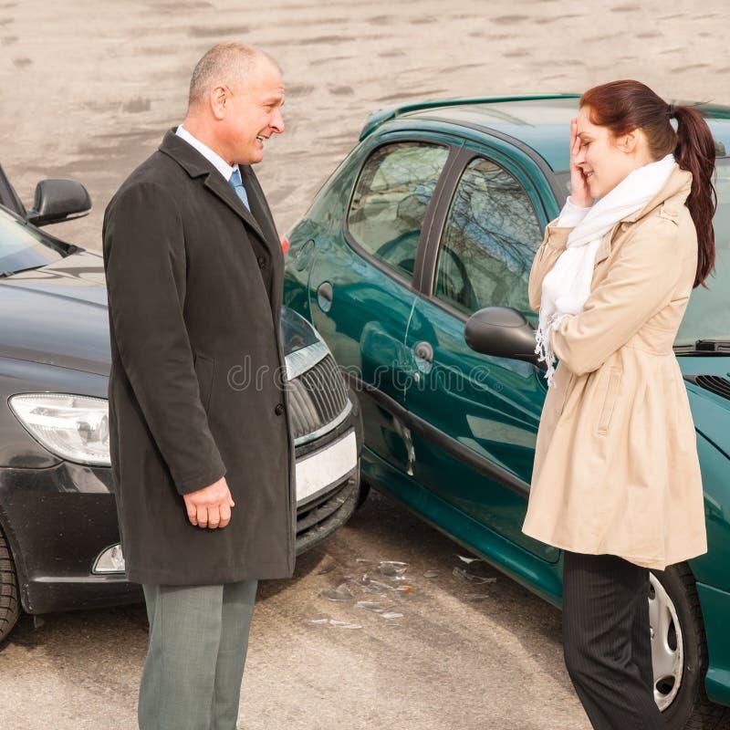 Hombre y mujer que hablan después de choque de coche foto de archivo