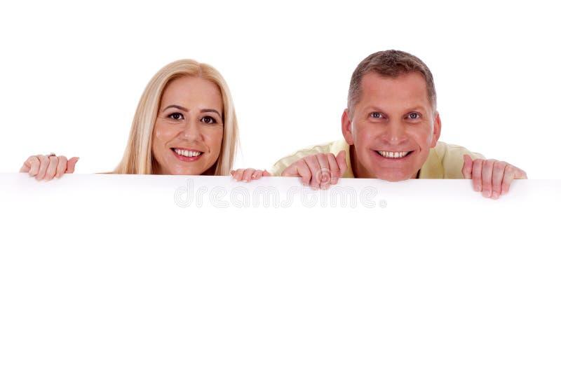 Hombre y mujer que llevan a cabo a la tarjeta blanca vacía imagen de archivo libre de regalías