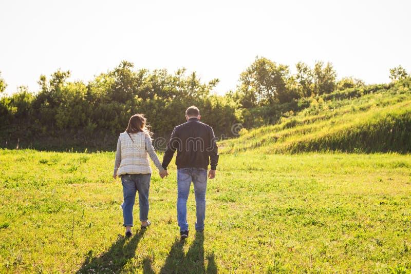 Hombre y mujer que llevan a cabo las manos y que caminan en la naturaleza, visión trasera fotos de archivo