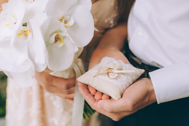 Hombre y mujer que llevan a cabo los anillos de bodas fotografía de archivo