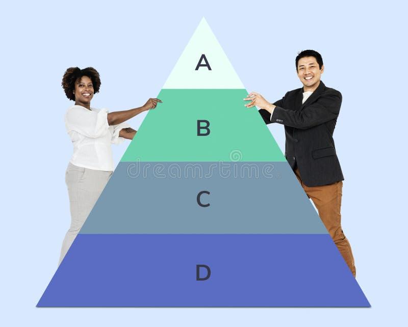 Hombre y mujer que llevan a cabo un gráfico de la pirámide foto de archivo libre de regalías