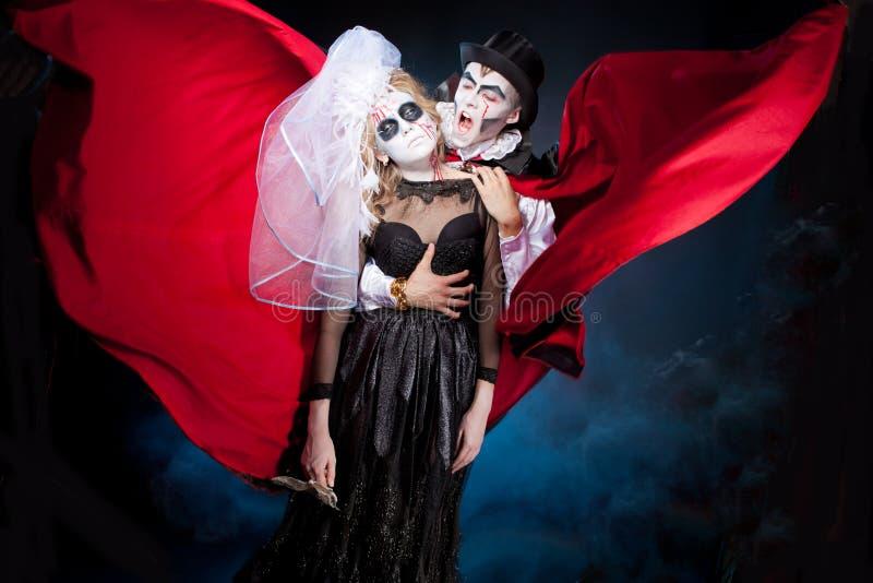 Hombre y mujer que llevan como vampiro y bruja. Halloween foto de archivo