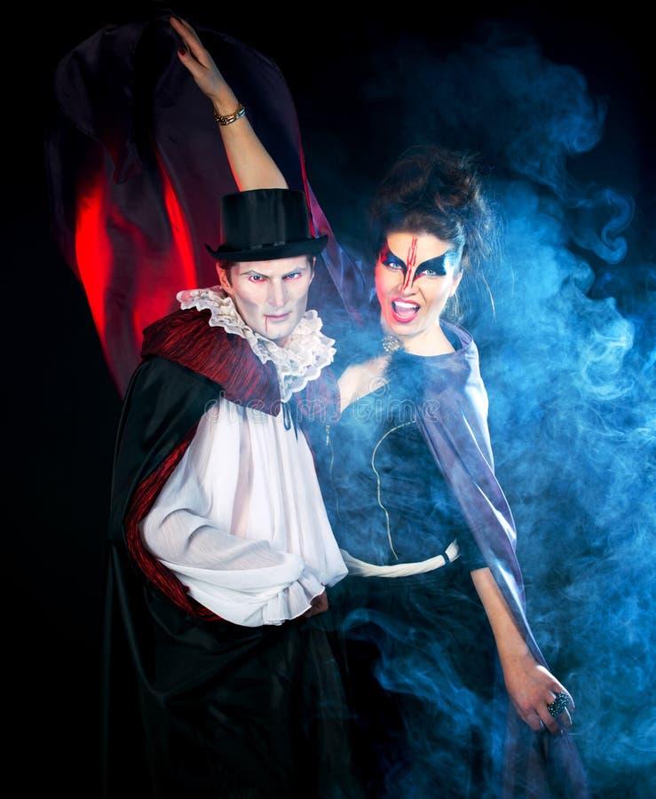 Hombre y mujer que llevan como vampiro y bruja. Halloween fotos de archivo