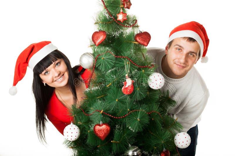 Hombre y mujer que miran fuera del árbol de navidad imagenes de archivo