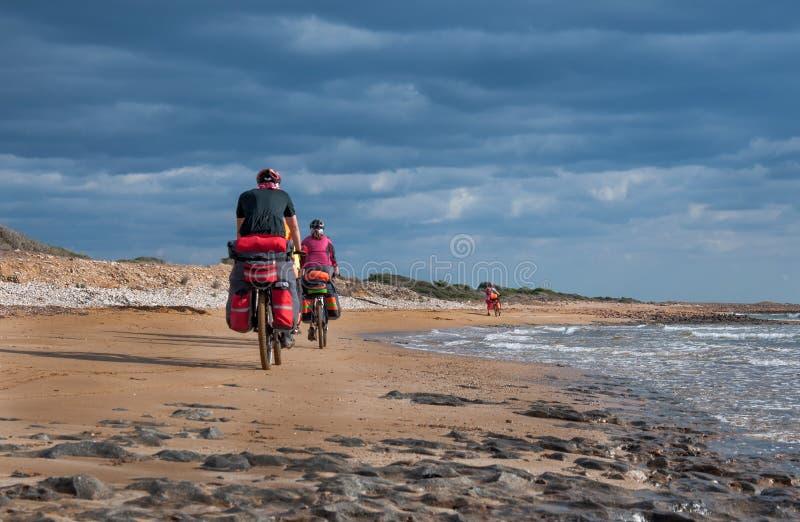 Hombre y mujer que montan la bici de montaña de la playa arenosa con la mochila fotografía de archivo