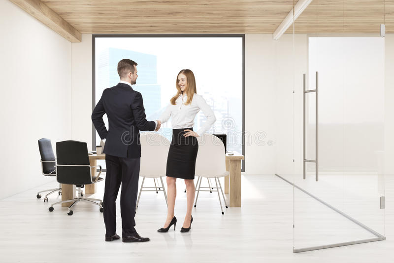 Hombre y mujer que sacuden las manos en sala de juntas con la ventana cuadrada foto de archivo libre de regalías