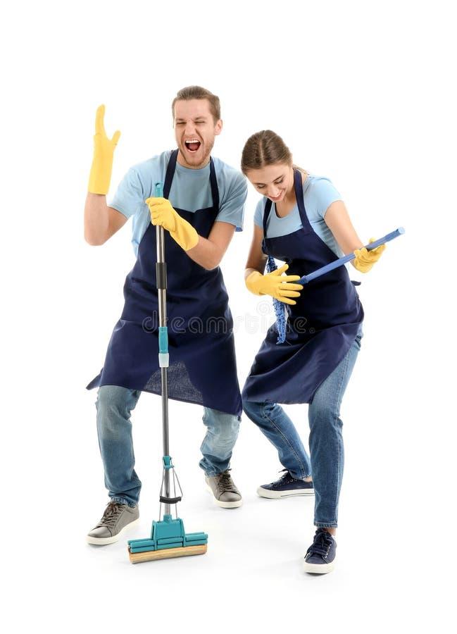 Hombre y mujer que se divierten con las fuentes de limpieza en el fondo blanco fotografía de archivo libre de regalías