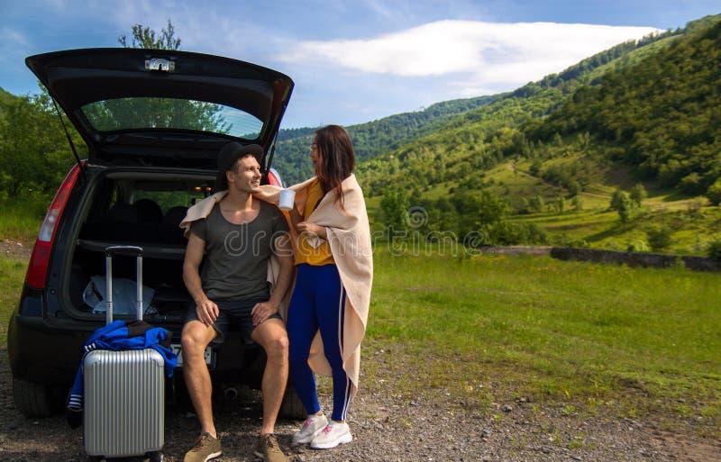 Hombre y mujer que se sientan en tronco de coche cerca de la montaña imagenes de archivo
