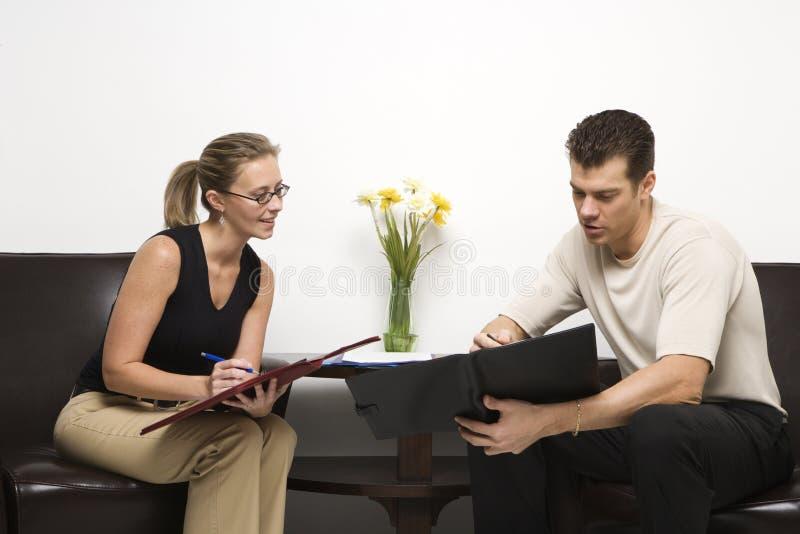 Hombre y mujer que se sientan mirando listas. foto de archivo